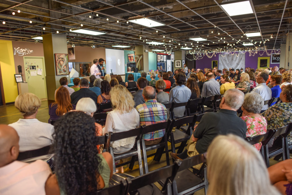 This photo shows the possibilities for a well-attended event in one of the Summit Artspace rental spaces. There are comfortable chairs in well-spaced rows set up for an audience in front of speakers in a unique, colorful and inspiring environment.